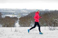 De winter die in park lopen: de gelukkige actieve jogging van de vrouwenagent in sneeuw met Kyiv-de mening van de stadshorizon, o Stock Afbeeldingen