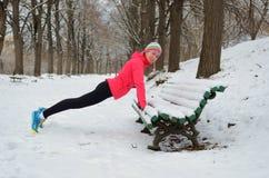 De winter die in park lopen: gelukkige vrouwenagent die en vóór het aanstoten in sneeuw, openluchtsport en fitness opwarmen uitoe Stock Afbeeldingen