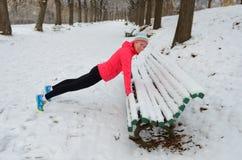 De winter die in park lopen: gelukkige vrouwenagent die en vóór het aanstoten in sneeuw opwarmen uitoefenen Royalty-vrije Stock Fotografie