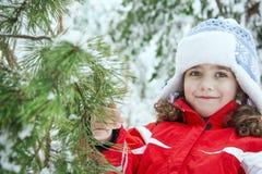 In de winter, in een bos, bevindt een klein mooi meisje zich dichtbij een speld Royalty-vrije Stock Foto's