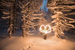 De winter fairytale, behandelde de zware sneeuwval de bomen en de huizen in het bergdorp de meisjesgloed trekt hart stock foto's