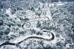 De winter gebogen windende die weg in het bos in sneeuw wordt behandeld Royalty-vrije Stock Fotografie