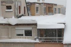 De winter Gevaarlijke sneeuwdalingen van de daken van de gebouwen De winter met zware sneeuwval Ijzige daken Gevaarlijke ijskegel royalty-vrije stock fotografie