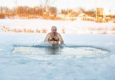 De winter het zwemmen Mens in een ijs-gat Stock Foto