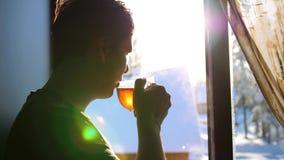 De winter ijzige dag De kerel vroeg in de ochtend die zich bij het venster en het drinken de hete thee bevinden stock video