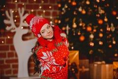 De winter, Kerstmisportret: De jonge vrouw kleedde zich in rode warme wollen cardigan, handschoenen en hoed die binnen dichtbijge Stock Afbeelding