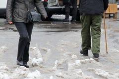 De winter De mensen lopen op een zeer sneeuwstoep Mensenstap op een sneeuw-verdwaalde weg Ijzige stoep Ijs op stoepen royalty-vrije stock fotografie
