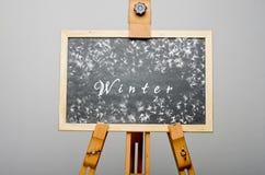 De winter op zwart bord met rond sneeuwvlokken wordt geschreven die Royalty-vrije Stock Foto
