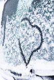 De winter, sneeuw, koude op het autoglas geschilderde hart er zijn het stemmen royalty-vrije stock afbeeldingen