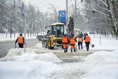 In de winter, in sneeuwstorm, maken de arbeiders en een tractor de weg Fr schoon Stock Fotografie