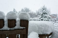 De winter, sneeuwval in de tuin Lijst en stoelen met sneeuw Stock Foto's