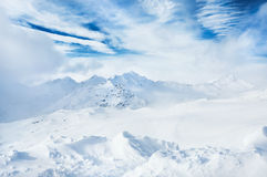 De winter snow-covered bergen en blauwe hemel met witte wolken Royalty-vrije Stock Fotografie
