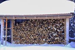 De winter, snow-covered stapel van brandhout onder een snow-covered dak, Beieren, Duitsland stock afbeelding