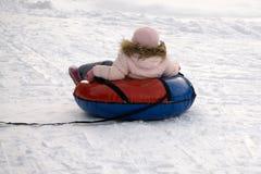 De winter, vrije tijd, sport, vriendschap en mensenconcept - gelukkige mensen die rond op sneeuwbuizen glijden Stock Foto