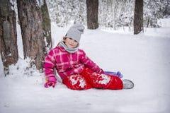 In de winter, zit een gelukkig meisje in een sneeuwbos onder een boom royalty-vrije stock afbeelding