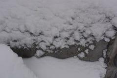 De winterachtergrond, aanhangende sneeuw, mooie besnoeiing van grote sneeuw op een blad van de metaalbouw met hopen en holten royalty-vrije stock foto