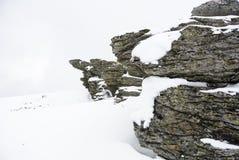 De winterachtergrond met rotsen in sneeuw worden behandeld die stock foto's