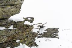 De winterachtergrond met rotsen in sneeuw worden behandeld die stock afbeeldingen