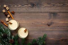 De winterattributen Glazen klassieke eierpunch met kruiden dichtbij nette tak op donkere houten hoogste mening als achtergrond co stock afbeelding