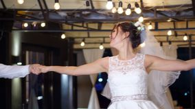 De winteravond, een terras met gloeilampen, in de straat wordt verfraaid, zijn de jonggehuwden dansend hun eerste huwelijksdans d stock videobeelden
