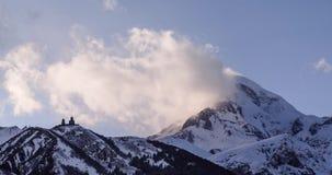 De winterberg Kazbek met sneeuw, wolkenlooppas, en oude kerk stock videobeelden