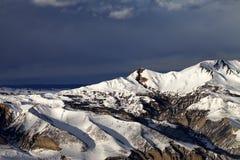 De winterbergen bij zonavond en donkere wolken Royalty-vrije Stock Afbeeldingen