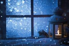 De winterdecoratie met een kandelaar dichtbij het snow-covered venster Stock Fotografie
