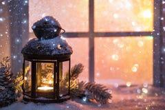De winterdecoratie met een kandelaar dichtbij het snow-covered venster Stock Foto