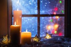 De winterdecoratie met kaarsen dichtbij het snow-covered venster Royalty-vrije Stock Foto
