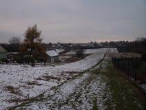 De wintergebied en bos op de achtergrond met een aardige mist Roze gevoelige hemel in de vroege ochtend en de mist stock afbeelding