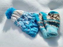 De winterkleren, gebreide hoed en vuisthandschoenen in de sneeuw stock foto's