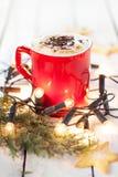 De winterkoffie in een rode mok met Kerstmislichten en koekjes stock fotografie