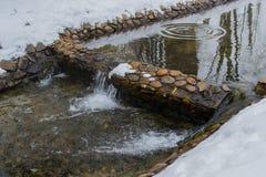 De winterkreek met een waterval en een bezinning van bomen Stock Afbeeldingen