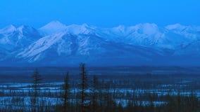 De winterlandschap in de bergen bij schemering in Yakutia, Siberië, Rusland royalty-vrije stock fotografie