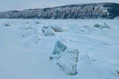 De winterlandschap in blauwe tonen met geribbeld ijs op de bevroren rivier bij schemering stock foto