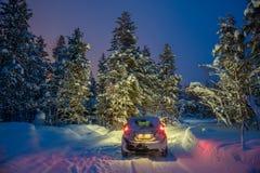 De winterlandschap met auto die - bij nacht drijven royalty-vrije stock foto's