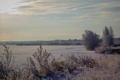 De winterlandschap met bevroren rivier en bos in de vorst royalty-vrije stock afbeeldingen