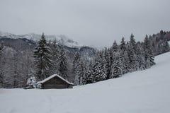 De winterlandschap met blokhuis, bomen en bergen op achtergrond dichtbij garmisch-Partenkirchen duitsland Stock Foto's
