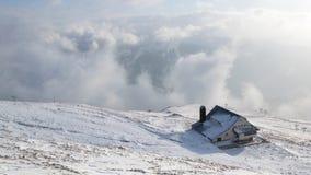 De winterlandschap met een huis op de berg met nevel en sneeuw stock afbeeldingen