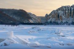 De winterlandschap met geribbeld ijs op de bevroren rivier bij zonsondergang royalty-vrije stock afbeelding