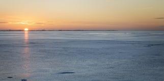 De winterlandschap met meer en zonsonderganghemel Stock Afbeeldingen