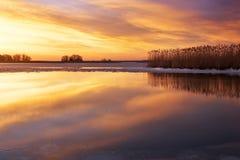 De winterlandschap met rivier, riet en zonsonderganghemel Stock Foto