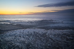 De winterlandschap met zonsondergang en bevroren meer Stock Afbeelding