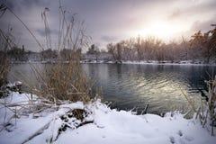 De winterlandschap met zonsopganghemel en rivier stock afbeelding