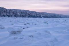 De winterlandschap in purpere tonen met geribbeld ijs op de bevroren rivier bij zonsondergang royalty-vrije stock afbeeldingen