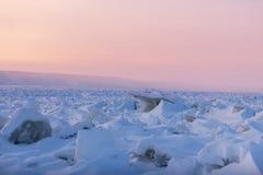 De winterlandschap in roze tonen met geribbeld ijs op de bevroren rivier bij zonsondergang stock afbeelding