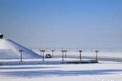De winterlandschap van een rivier die met ijs en sneeuw wordt behandeld, een promenade met uitstekende lantaarns en een piramide  stock foto's