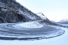 De winterlandschap van een sneeuwwegkromming in Noorwegen stock foto