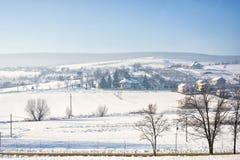 De winterlandschap van het dorp van Roemenië met sneeuw stock afbeelding