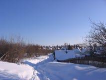De winterlandschap van het Russische dorp in de sneeuw-betreden weg door de afwijkingen op een duidelijke Zonnige dag in landelij royalty-vrije stock fotografie